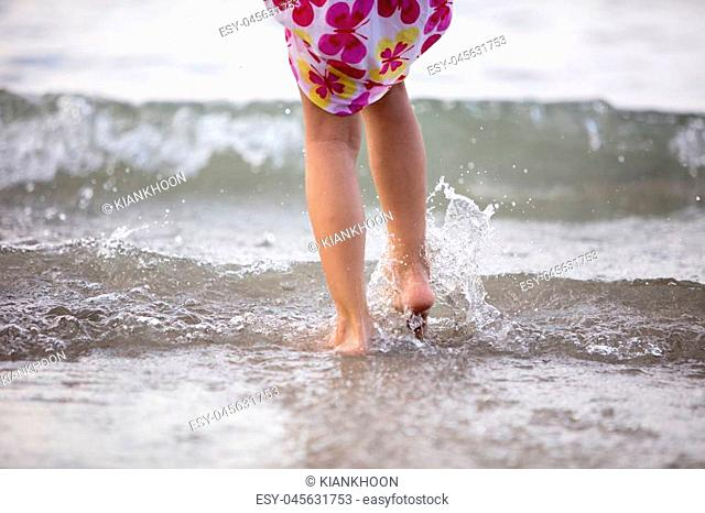 Asian Chinese little sisters playing water at beach outdoor