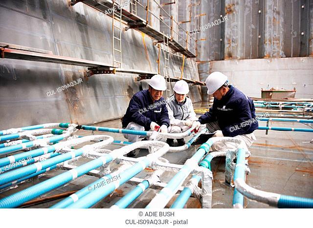 Workers checking pipework on container ship at shipyard, GoSeong-gun, South Korea