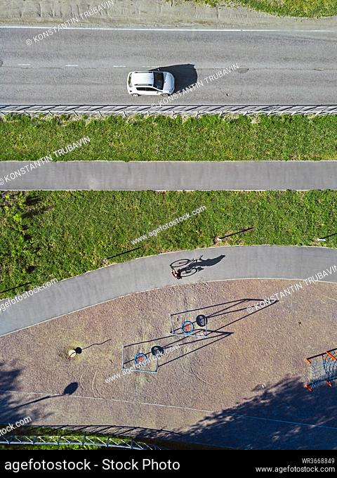 Russia, Tikhvin, Man riding bicycle on path near park playground, aerial view