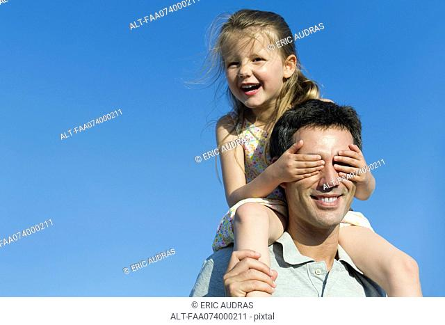 Girl covering father's eyes with her hands