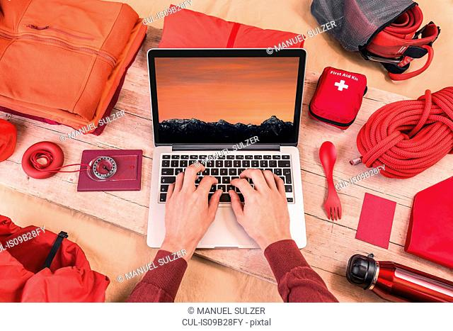 Overhead view of man's hands typing on laptop whilst preparing climbing equipment for travel