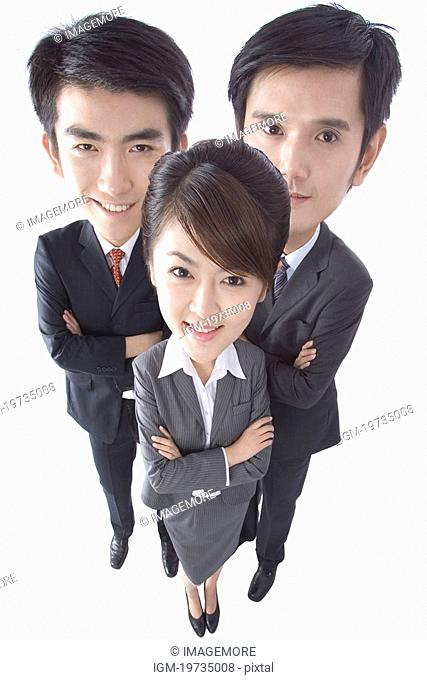 Three businesspeople standing with arms crossed