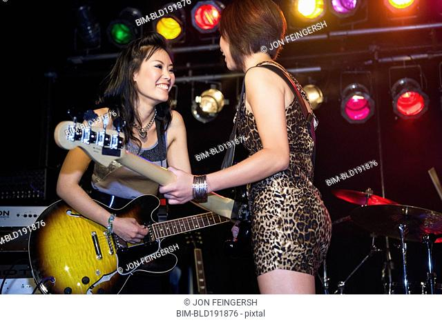 Asian women playing electric guitar onstage