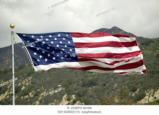 An American flag missing its lower stripes as it blows in the wind