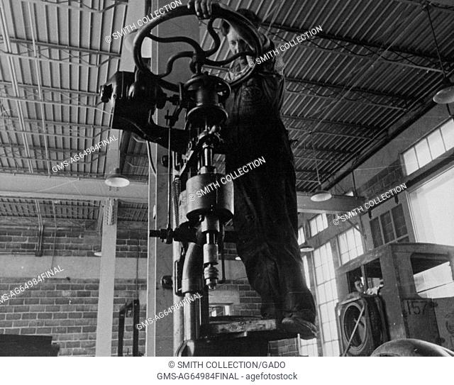 Worker standing on a large drill press and spinning a cast iron wheel, Beltsville, Maryland, 1935. From the New York Public Library