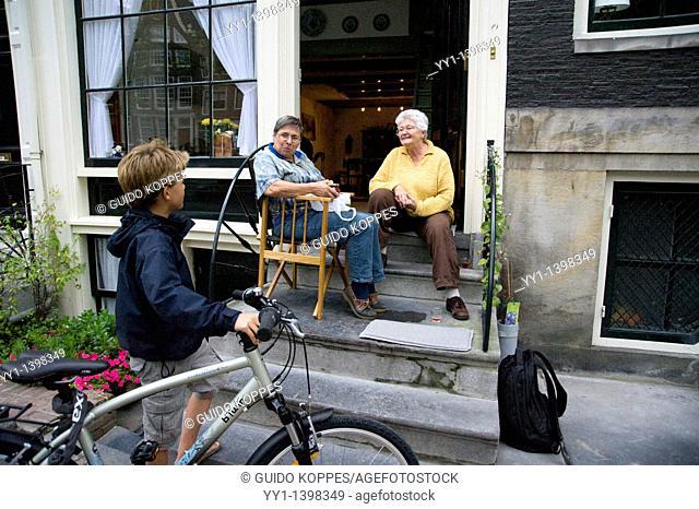 Amsterdam, Netherlands. Two elderly ladies having a conversation with their next-door neighbour tween boy