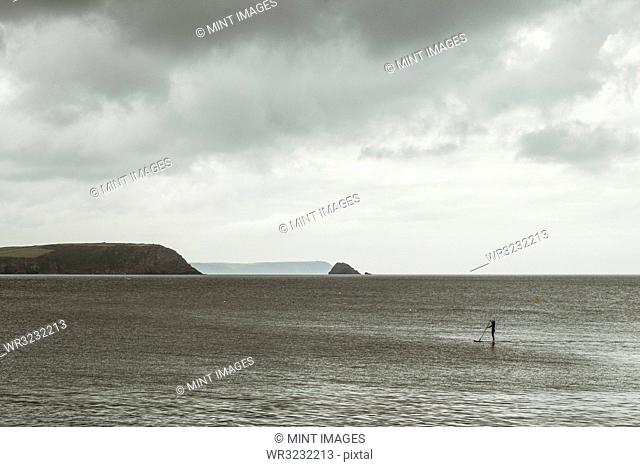 An overcast day with clouds, a view across a calm sea, to distant headlands and an island offshore, one person paddle boarding