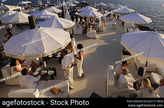 23 June 2020, Spain, Palma: Customers are at sunset in the Bar Purobeach in Cala Estancia on the beach Playa de Palma. Photo: Clara Margais/dpa