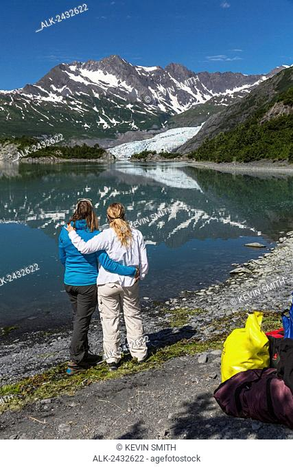 Two women embrace and enjoy the scenic view of Shoup Bay, Shoup Bay State Marine Park, Prince William Sound, Valdez, Southcentral Alaska