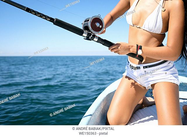 Close up of fishing reel and rod used by attractive young woman on fishing boat