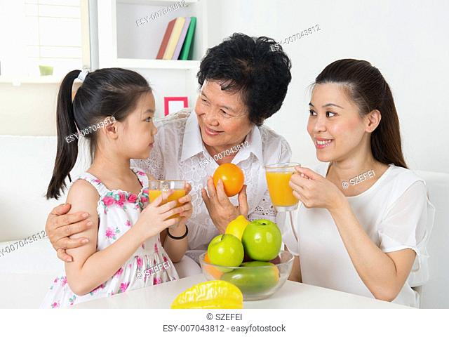 Asian family drinking orange juice. Happy Asian grandparent, parent and grandchild enjoying cup of fresh squeeze fruit juice at home