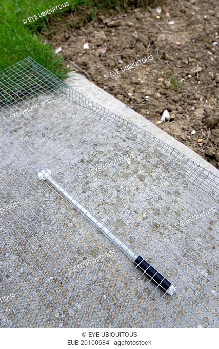 Thermometer beneath protective wire mesh laid on concrete to measure the minimum overnight concrete temperature beside patch of clear earth where the moisture...