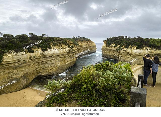 Two people taking in the view at Loch Ard Gorge on a cloudy day, Port Campbell National Park, Great Ocean Road, Victoria, Australia