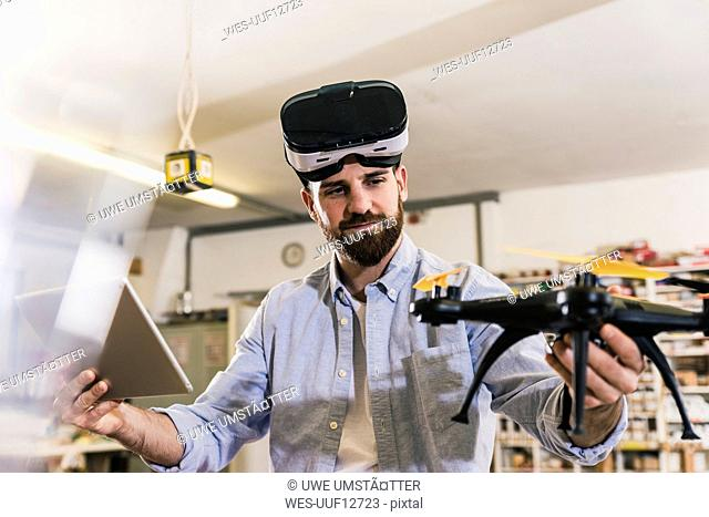 Man wearing VR glasses holding drone and tablet