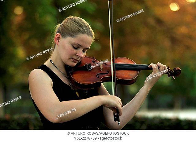 Girl playing violin in Retiro Park, Madrid. Spain