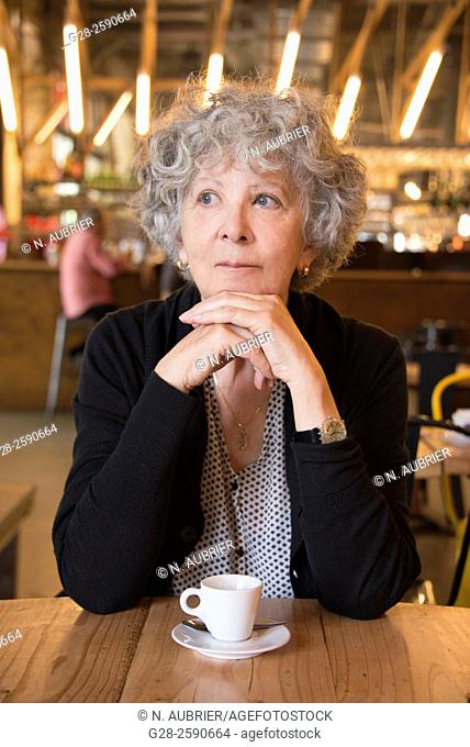 Beautiful senior woman, with grey hair, happy looking, thoughtful, with head resting on her clasped hands, elbows on table, in a cafe