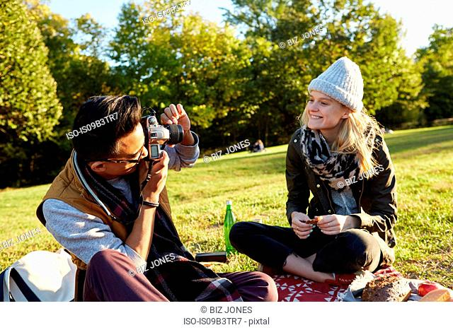 Mid adult man photographing girlfriend during park picnic