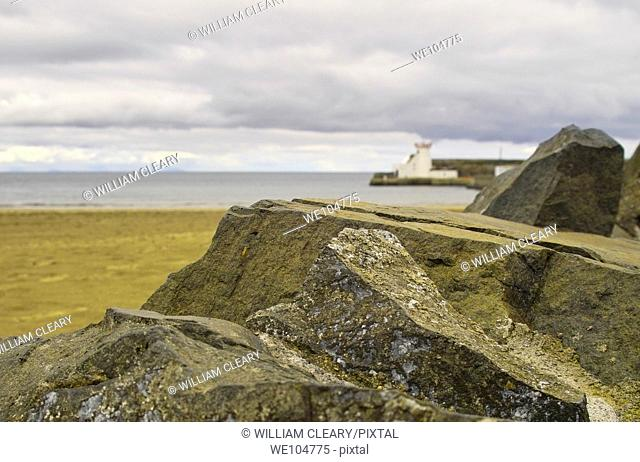The lighthouse in Balbriggan, Co  Dublin, Ireland, framed by rocks in the foreground