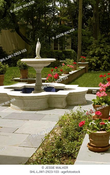 Gardens: Fountain patio area, large fountain gerometric shape, bluestone patio surround,potted red and pink geraniums