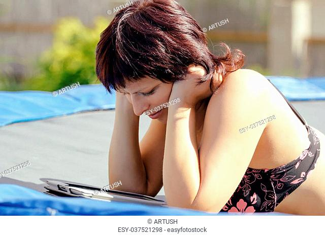 busty woman with swimsuit reading news on tablet outdoor