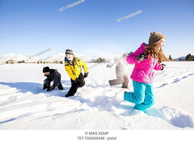 Children (8-9, 10-11) playing in snow