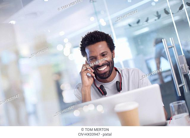 Smiling, confident creative businessman talking on smart phone at laptop in office