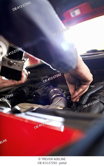 Close up mechanic arm reaching in car engine