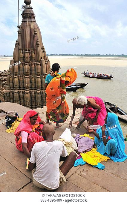 Pilgrims relaxing after bathing at the ghat by the Ganges river
