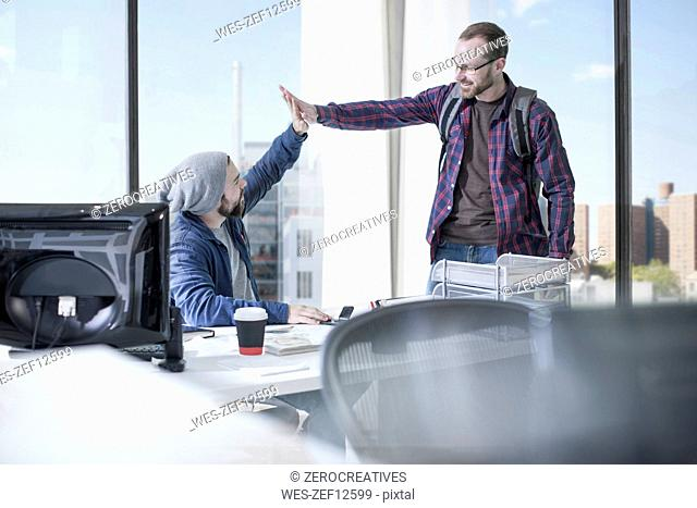 Colleagues in office high fiving