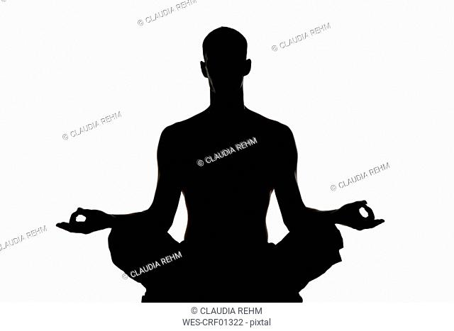 Man exercising yoga, silhouette