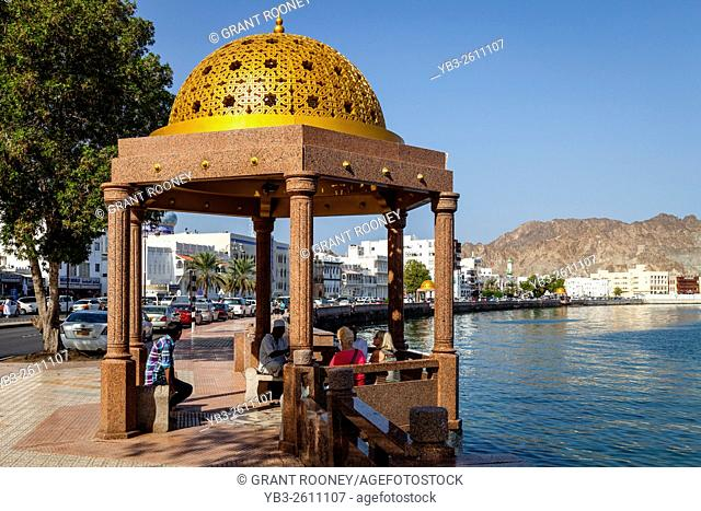 People Sitting Under A Colourful Sun Shelter, The Corniche (Promenade) At Muttrah, Muscat, Sultanate Of Oman