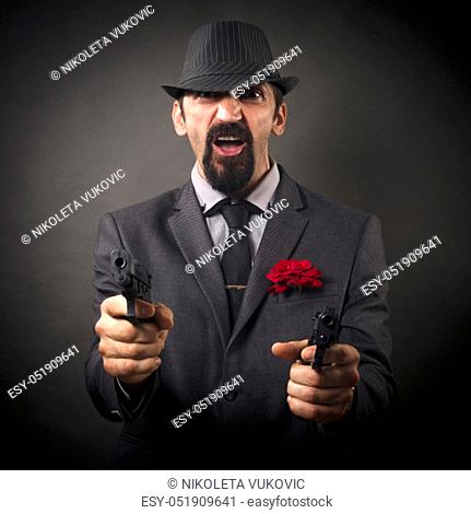 The elegant old-fashioned gangster or mafia boss in hat and suit is aiming with two pistols on dark gray background
