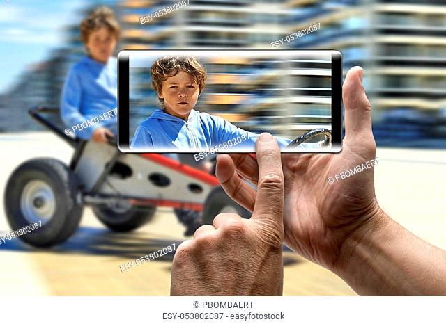 Two hands holding a mobile Smartphone and take a picture of a Young boy driving a pedal car