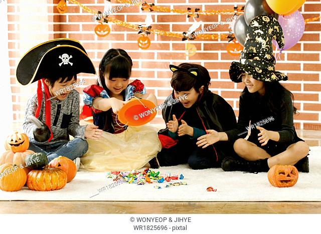 two girls and two boys playing in Halloween costumes