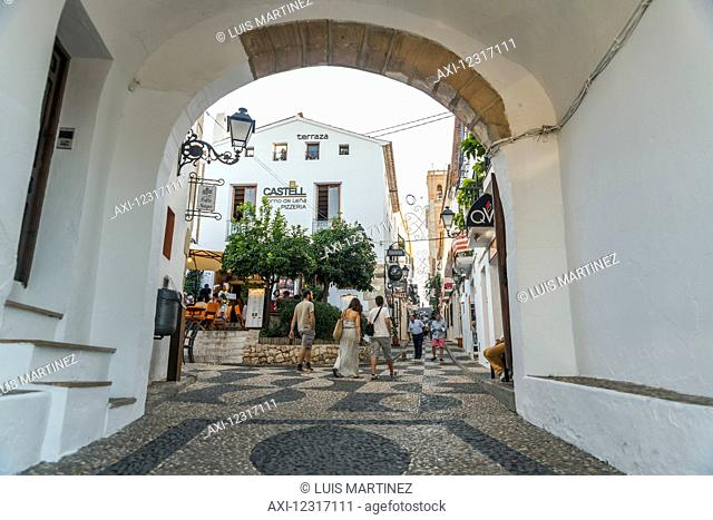 Pedestrians walking among buildings in Altea, a beautiful town in Costa Blanca, where many of the streets are sloped and the houses are painted with the typical...