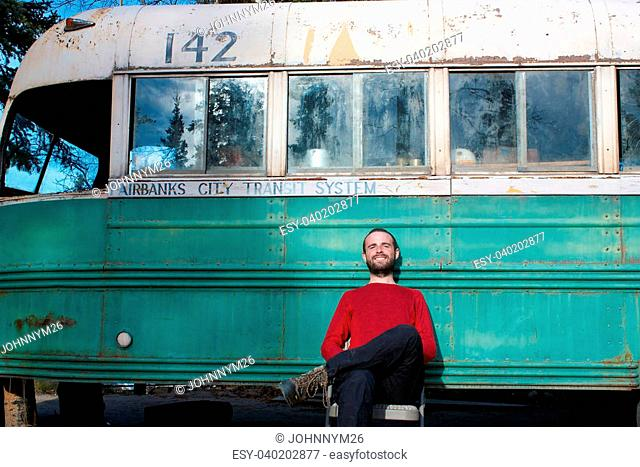 Young man sitting in front of the Magic Bus from the movie Into The Wild