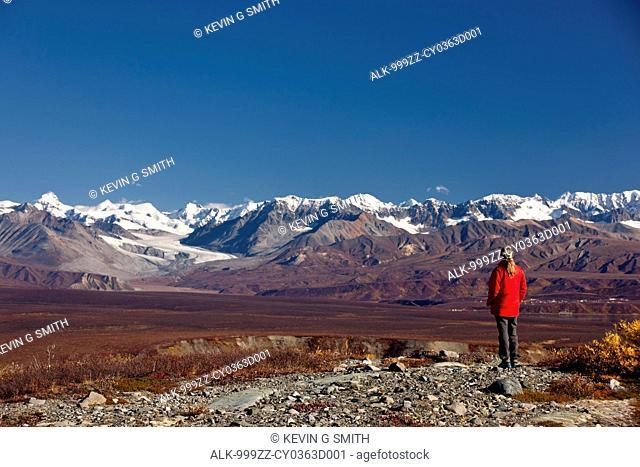 Woman enjoys the view of Summit Lake and the Alaska Range from the Denali Highway near Paxson, Interior Alaska, Autumn