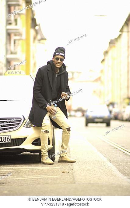 streetstyle, man leaning on taxi car at street, in city Munich, Germany