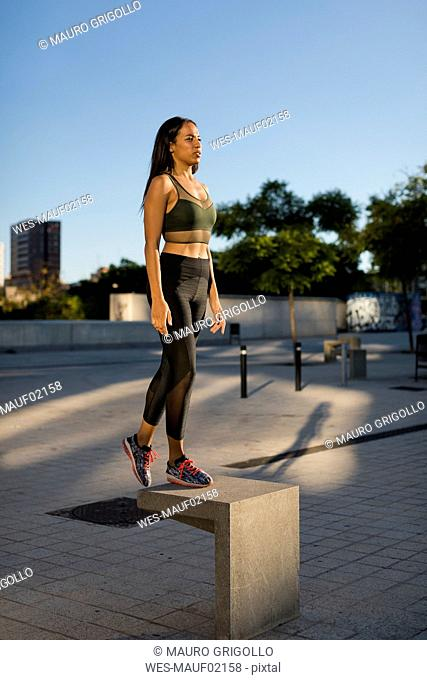 Sporty young woman standing on concrete block in the city