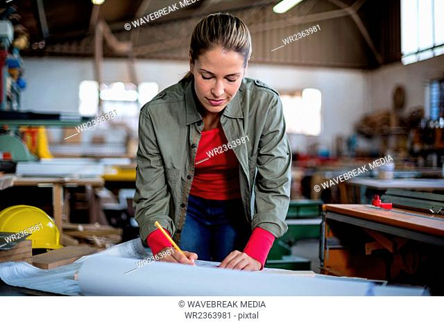 Female carpenter marking on blueprint