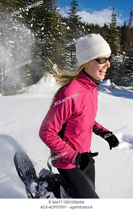 Young woman snowshoeing on blue day, Sun Peaks Resort, British Columbia, Canada