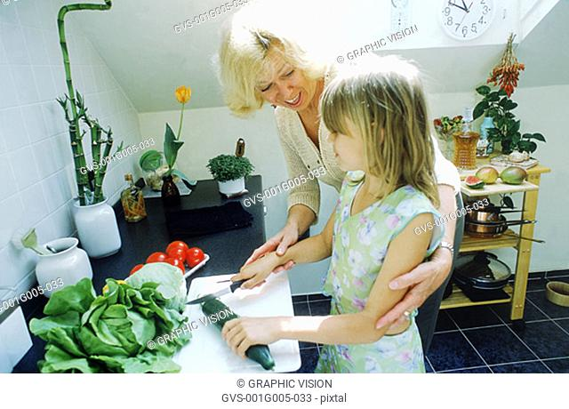 Grandmother helping granddaughter in the kitchen