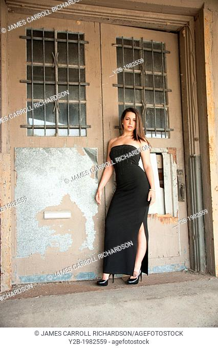Caucasian woman wearing black dress standing in front of warehouse door in urban Memphis Tennessee USA