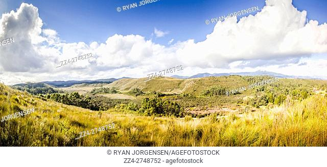 Wide angle landscape panoramic on a open country grassland hitting ruggered mountainous terrain. Parting Creek Regional Reserve, Zeehan, Tasmania, Australia