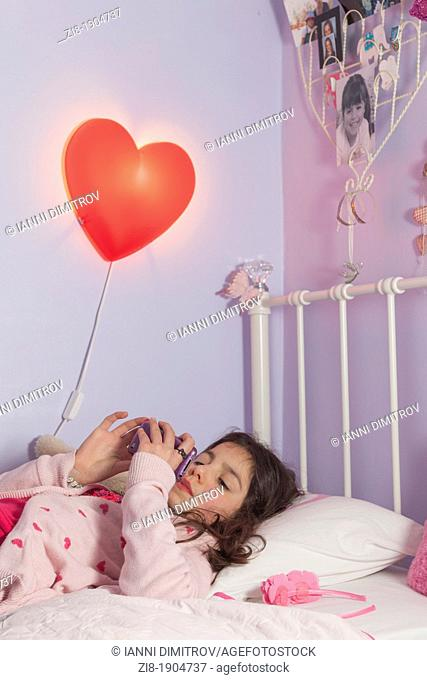 Adolecent girl playing games on her mobile phone in bed