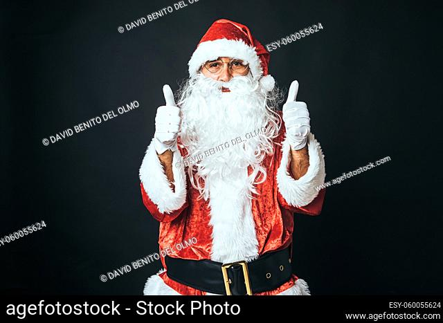 Man dressed as Santa Claus with thumbs up, on black background. Christmas concept, Santa Claus, gifts, celebration