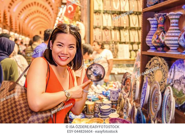 Beautiful Chinese woman buys souvenirs sold in Egypt Bazaar in Eminonu,Istanbul,Turkey