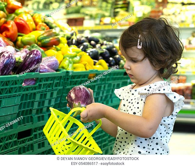 Child shopping eggplants in supermarket. Concept for buying fruits and vegetables in hypermarket. Little girl hold shopping basket