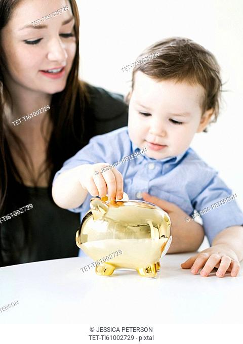 Mother teaching son (4-5) how to save money