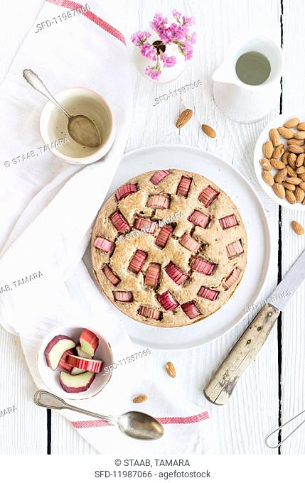 A whole rhubarb cake with almonds on a table